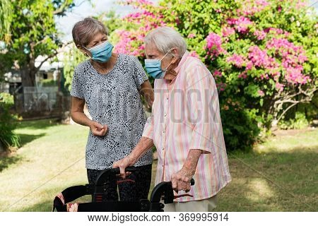 Carer Helping Elderly Lady To Get Exercise In Garden Wearing Mask