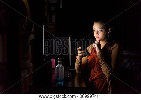 Young Beautiful Indian Woman Thinking While Using Phone And Working From Home Late At Night In The D