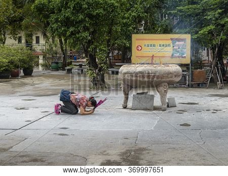 Gnong Ping, Lantau Island, Hong Kong, May 2018 - A Lady Praying At An Incense Urn At Po Lin Monaster