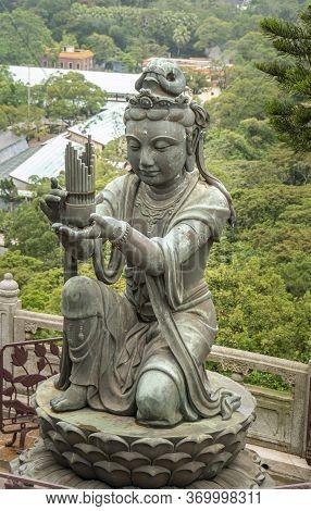 Buddhist Deva Statue Offering The Gift Of Music To The Tian Tan Big Buddha  Statue On Lantau Island,
