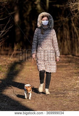 Young Woman In Warm Jacket, Wearing Virus Face Mouth Mask, Walks Her Dog On Country Road. Masks Are