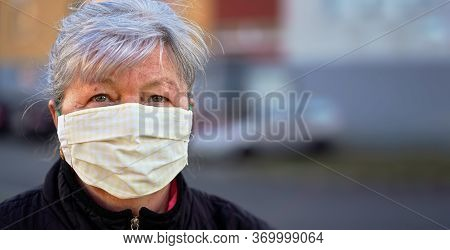 Elderly Senior Woman Wearing Home Made Cloth Face Mouth Nose Virus Mask Outside, Blurred Building Ba