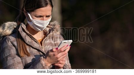 Young Woman In Warm Jacket, Wearing White Cotton Virus Face Mask, Checking Her Mobile Phone. Coronav