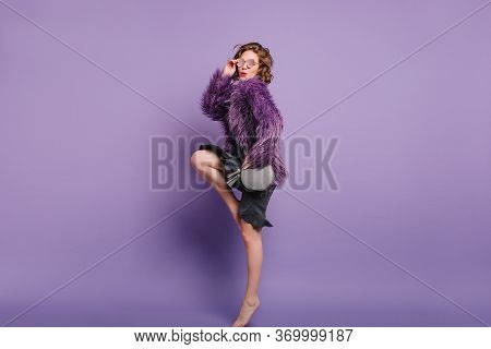 Full-length Portrait Of Barefooted Girl Standing On Top-toes During Photoshoot In Winter Jacket. Ind