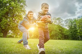 Father and son playing football, Father's day, Playful Man teaching Boy rugby outdoors in sunny day at public park. Family sports weekend.