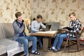 The Same Man. A Man Holds A Cat In His Arms. A Man Works At A Laptop. A Man In A Chair Reading A Boo
