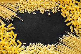 Raw Fusilli, Pipe Rigate And Spaghetti On A Black Slate Board With Copy Space.