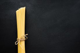 A Pack Of Spaghetti Tied With Twine On A Black Slate.