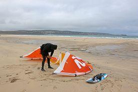 Kitesurfer Preparing Kite At Gwythian Beach In Cornwall