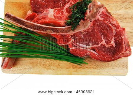 fresh raw meat : fresh red beef ribs with green sprouts on wooden board isolated over white background