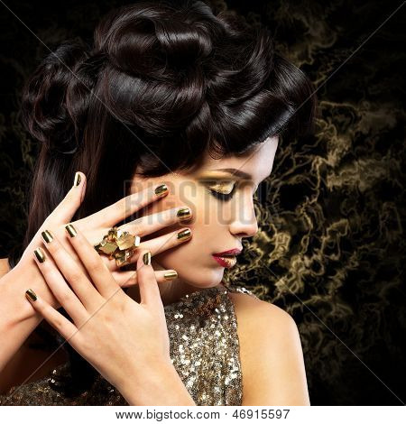 Beautiful woman with golden nails and fashion hairstyle over creative background poster