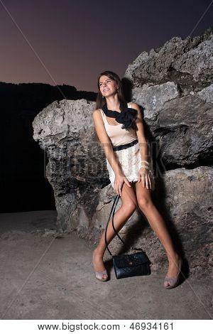 Woman Sitting On The Rocks