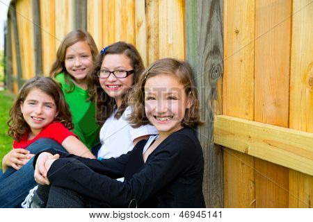Girls group in a row smiling in a wooden fence outdoor