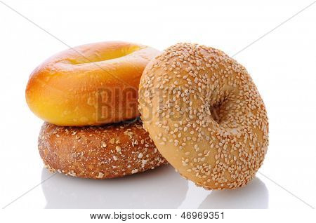 Three different bagels on a white surface with reflection. One each of an egg bagel, sesame seed, and mulit-grain Bagel are shown.