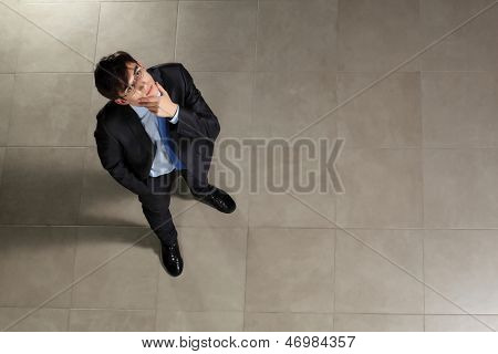 Image of young businessman in glasses looking thoughtfully. Top view