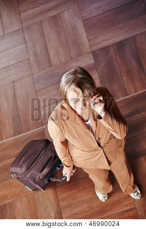 Old woman traveling with luggage talking on the phone