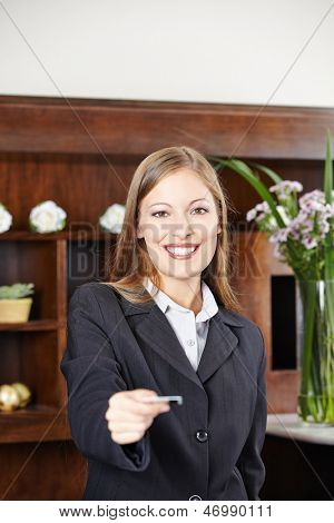 Smilinge female receptionist at hotel offering a key card