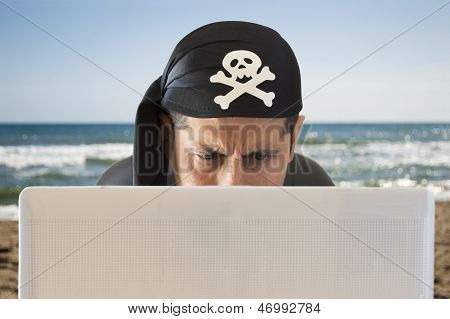 hacker looking confused on the beach to his computer