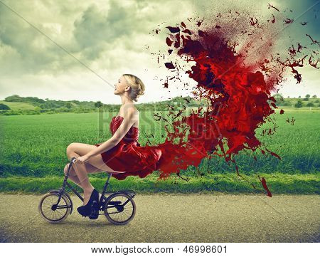 beautiful girl goes by bicycle with red dress