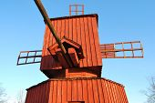 Tail and turning tower of ancient red wooden windmill. poster
