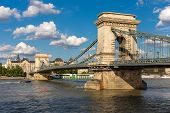 The Chain Bridge with a motorboat and Danube river in Budapest under a blue cloudy sky Hungary poster