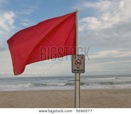 Red warning flag flying at the beach.