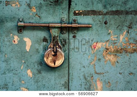 Padlock on a turquoise grungy door