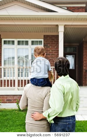 Familia feliz frente a casa