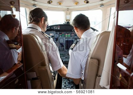 Rear view of pilot and copilot in cockpit of corporate jet