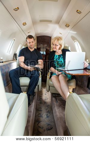 Young businessman showing something to female colleague on digital tablet in private jet