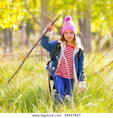 Hiking kid girl with backpack in autumn poplar trees forest and walking stick