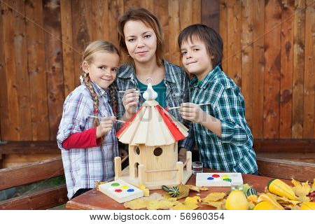 Woman with two kids preparing a bird house for the winter