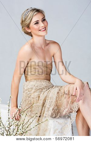 Beautiful young bright in tight golden minidress and embroidred lace sitting on studio background