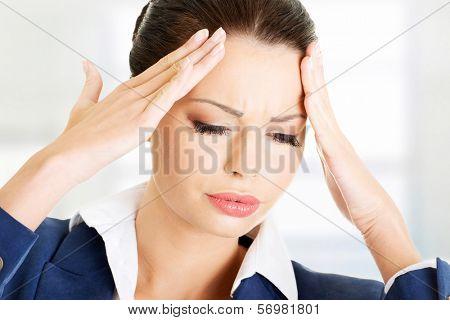 A businesswoman with a headache holding head