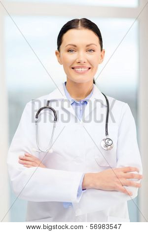 healthcare and medicine concept - smiling young doctor with stethoscope in cabinet