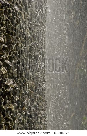 Water cascading down a constructed vertical rock face poster