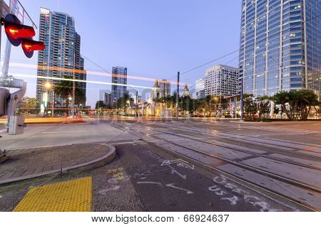 A street view of Downtown San Diego California USA at dusk. A night view of the transportation city lights and skyscrapers and local buildings in the Marina's waterfront. poster
