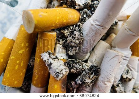 cigarette butts in an ashtray, symbol photo for chain smoking and health risk