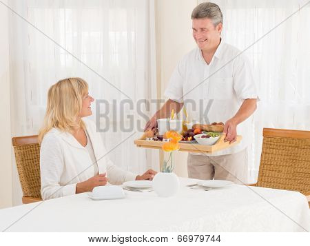 Smiling Mature Senior Husband Serving His Wife Healthy Breakfast