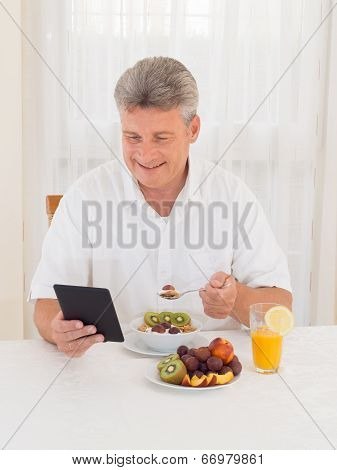 Mature Man Reading Book While Eating Breakfast