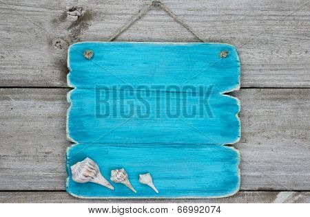 Blank teal blue sign with seashells hanging on rustic wooden background