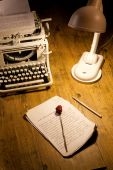 Old typing machine, lamp and manuscript on a wooden table poster