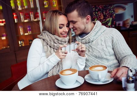 Couple drinking coffee and talking in caf���©