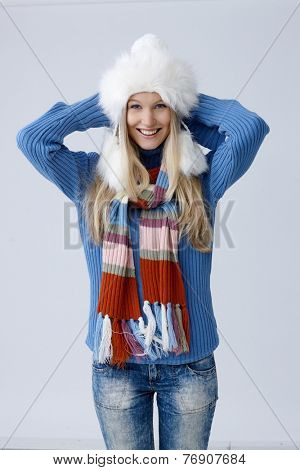 Happy young blonde woman standing in hat and scarf, folding arms around scruff, smiling, looking at camera.