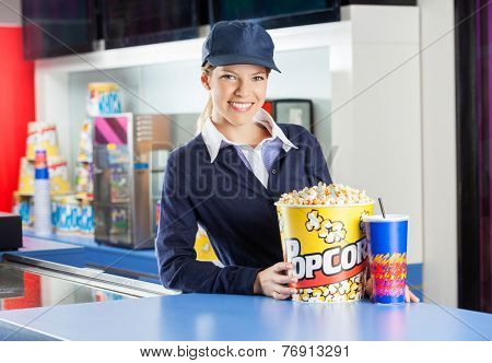 Portrait of smiling worker with popcorn bucket and drink at cinema concession counter