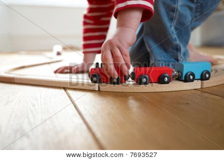 Child Playing With Toy Wooden Train