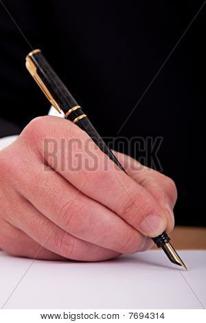 Businessman Signing A Document  With A Fountain Pen Isolated On A White Background. Studio Shot