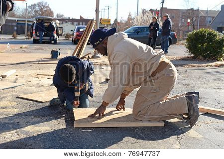 FERGUSON, MO/USA - NOVEMBER 25, 2014: A child and man work to assemble boards for windows of business in the aftermath of vandalism after grand jury decision not to indict Ferguson police Wilson.