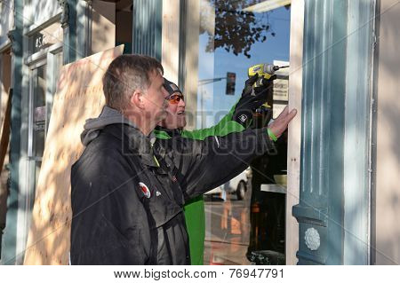 FERGUSON, MO/USA - NOVEMBER 25, 2014: Men work to board up windows in Ferguson as business in the aftermath of riots.