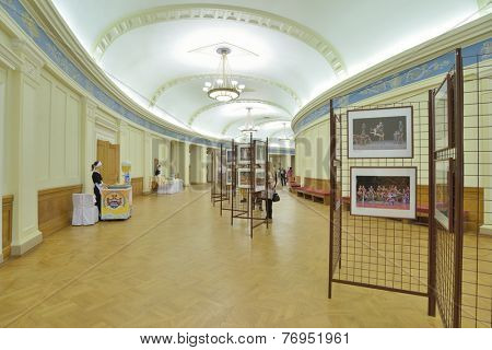 NOVOSIBIRSK, RUSSIA - NOVEMBER 8, 2014: People looking at photo exposition before the spectacle in the Opera and Ballet Theater. It is the largest theatrical building in Russia